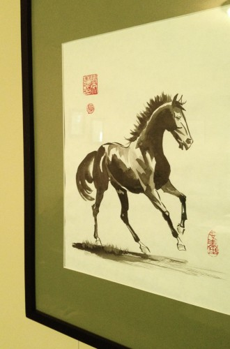 Framed Chinese watercolor painting of a galloping horse.  The frame is 12x16 inches and simple black wood with a sage green matt.